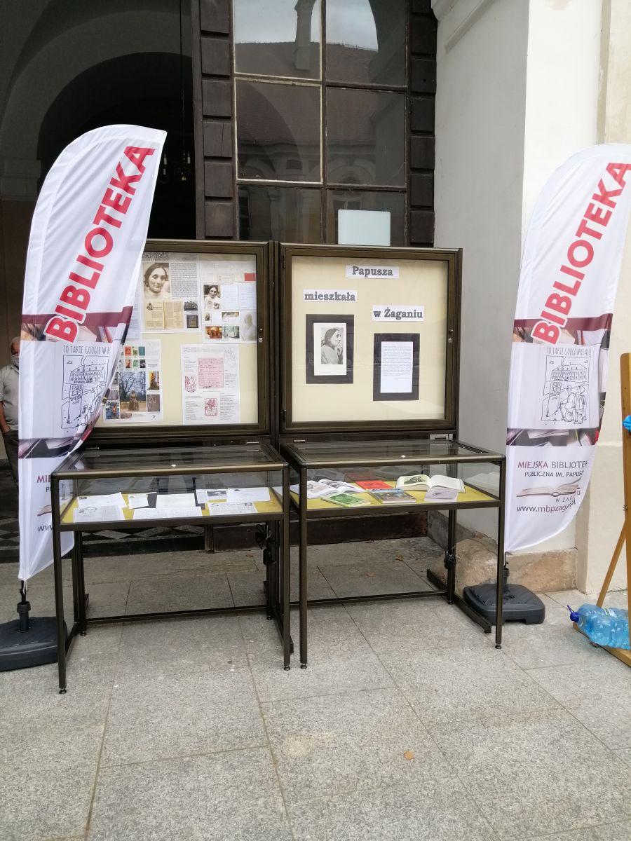 Zdjęcie wystawy o Papuszy. Dwie gabloty pionowe i poziome oszklone z materiałami o Papuszy: zdjęcia, artykuły, książki, kserokopie listów. Po obu stronach wystawy pionowe materiałowe banery z nazwą biblioteki. ,