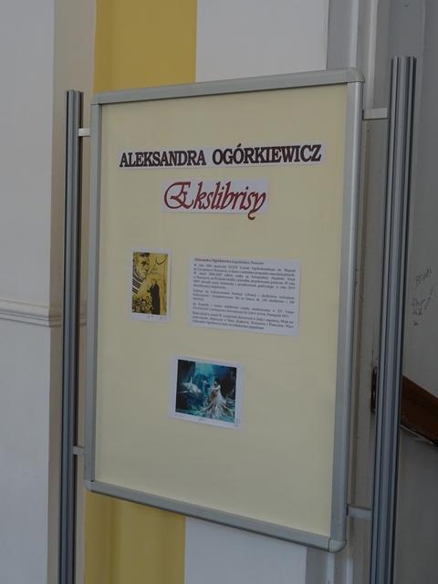 Zdjęcie tablicy informacyjnej o wystawie. W holu po prawej stronie przed wejściem do Biblioteki. Na tablicy dużymi literami na czerwono nazwisko artystki, poniżej ozdobną czcionką duży napis Ekslibrisy. Jeszcze niżej po lewej ekslibris, obok biogram autorki. Na dole ekslibris.