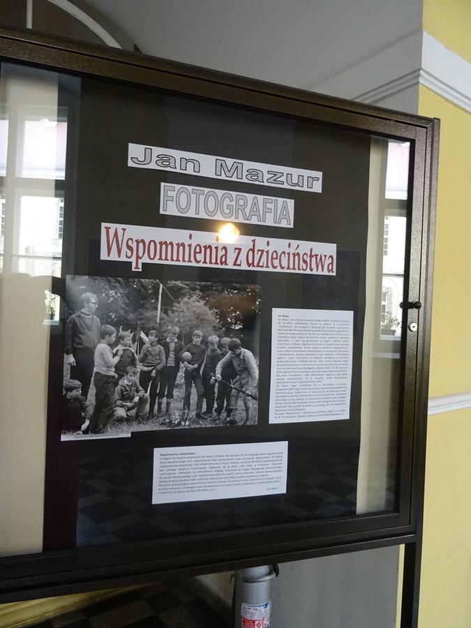 Zdjęcie tablicy głównej z informacjami o wystawie, autorze fotografii i jednym grupowym zdjęciem uczestników Nieobozowego Lata.