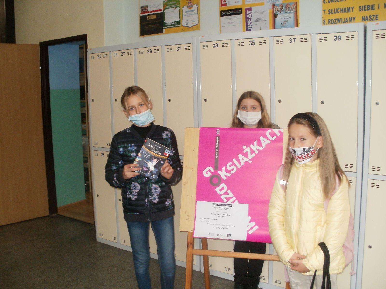 Zdjęcie. W korytarzu szkolnym, na tle szafek w szatni i szkolnych gazetek nad nimi pozuje troje dzieci trzymając przeczytaną książkę. Na pierwszym planie pomiędzy dziećmi na sztaludze widoczna tablica z różowym plakatem Godzinami o Książkach.