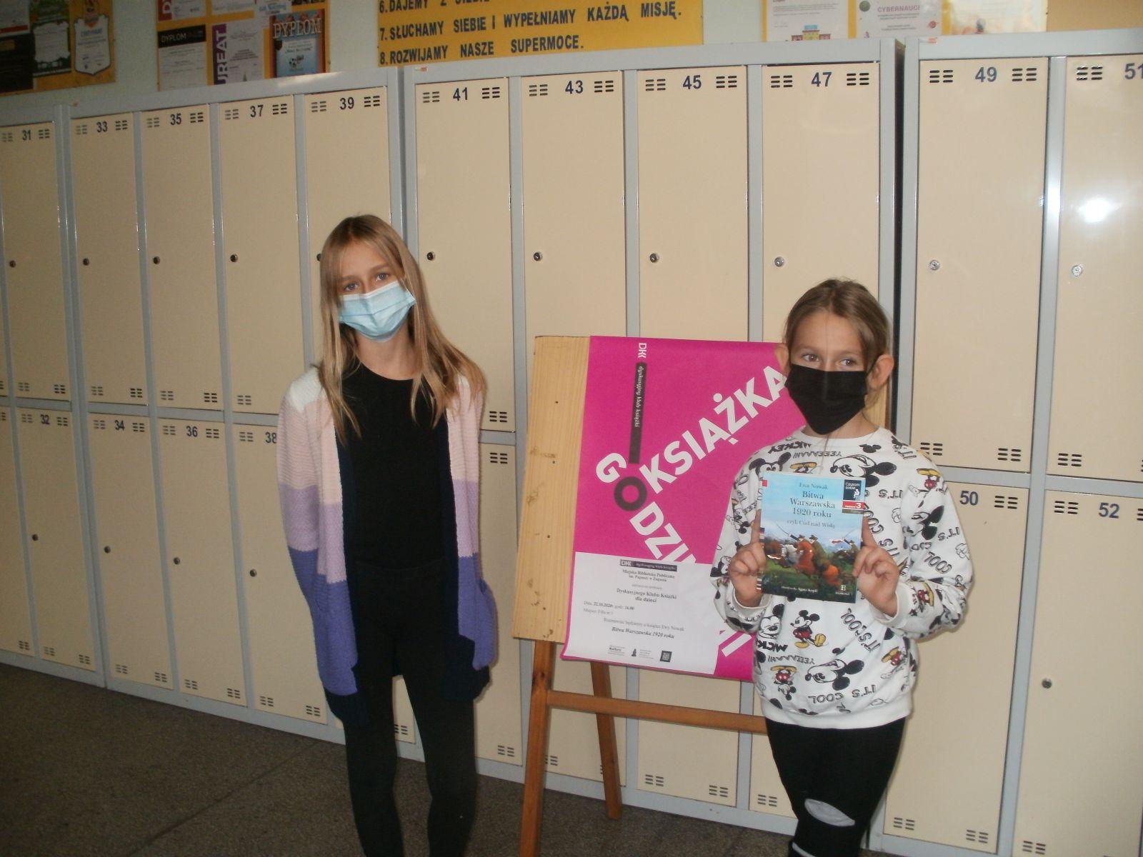 W korytarzu szkolnym, na tle szafek z szatni i wiszącymi nad nimi gazetek szkolnych pozują dwie dziewczynki z przeczytaną książką i w maseczkach na nosie i ustach. Pomiędzy nimi, na pierwszym planie sztaluga z tablicą i umieszczonym na niej różowym plakacie Godzinami o Książkach.