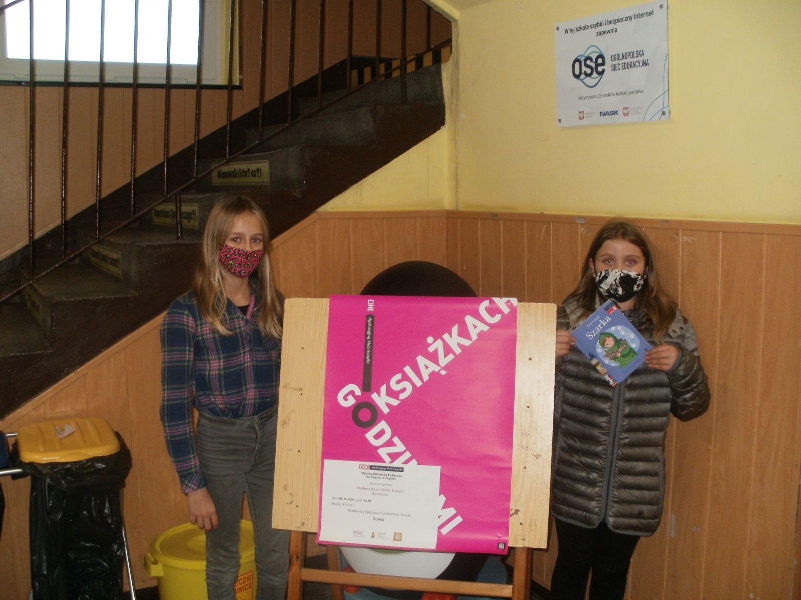 Zdjęcie. Na szkolnym korytarzu, w kącie przy schodach prowadzących na piętro pozują dwie dziewczynki trzymające przeczytaną książkę. Pomiędzy nimi stoi sztaluga z różowym plakatem Godzinami o Książkach.