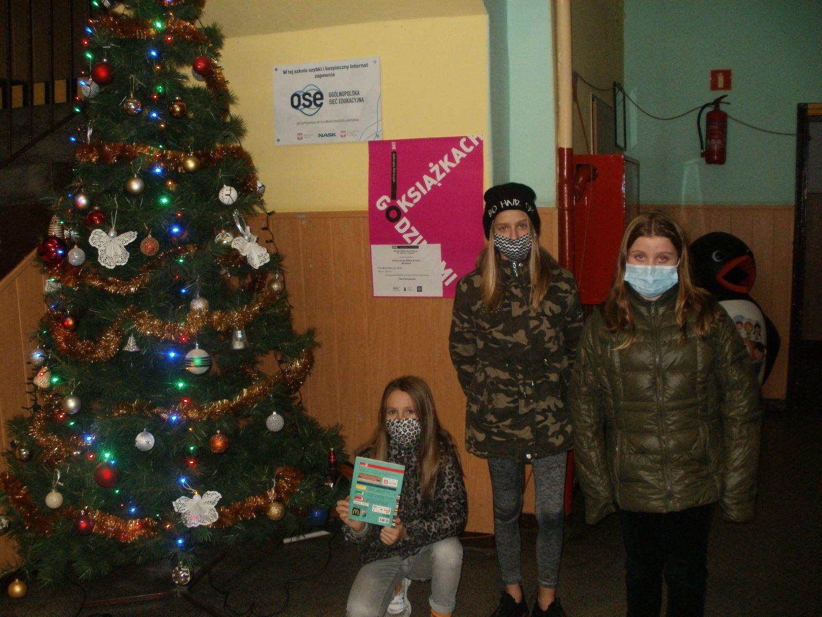 Zdjęcie. W korytarzu szkolnym, obok świątecznie przystrojonej choinki i na tle  różowego plakatu O książkach Godzinami pozują trzy uczennice z przeczytana książką. Dwie stoją, a jedna w pozycji kucającej. Dzieci są ciepło ubrane, w kurtkach i w maseczkach na twarzy.