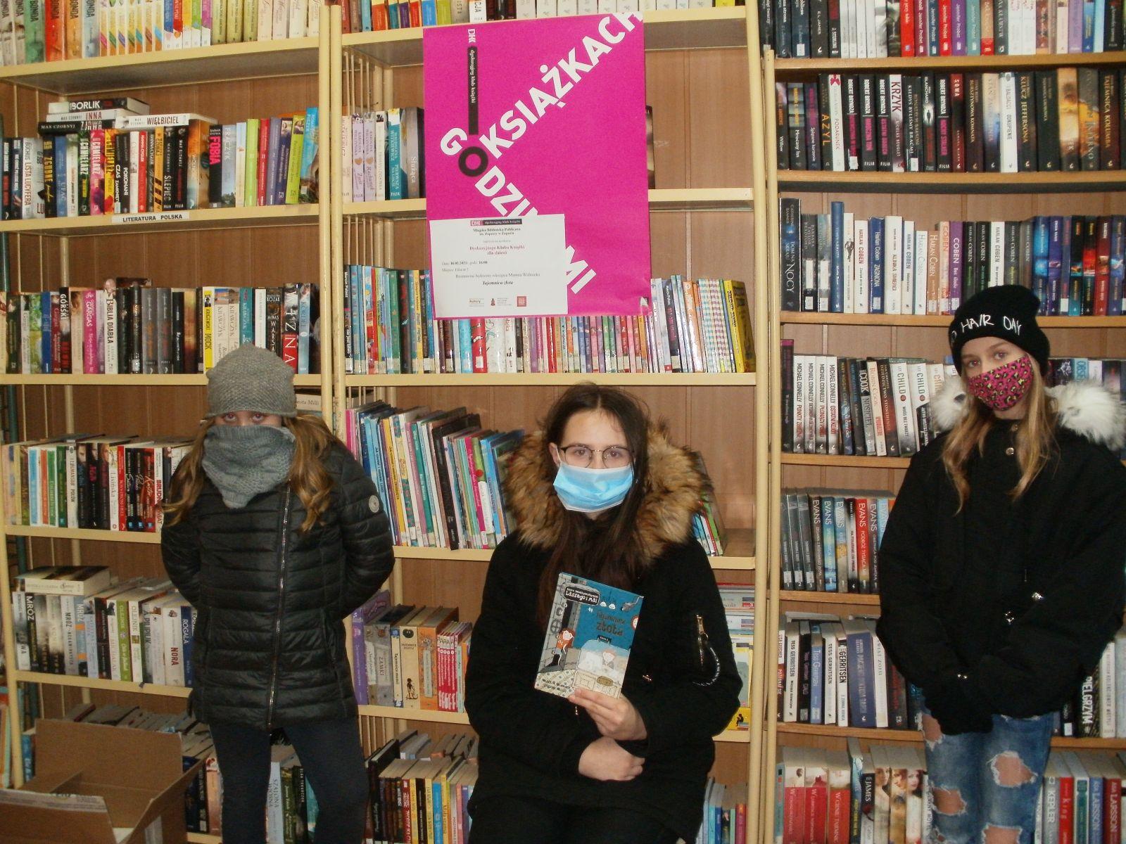 Zdjęcie. Na tle bibliotecznych regałów z książkami i różowego plakatu O książkach godzinami, pozują trzy uczennice. Stojąca w środku trzyma przeczytaną książkę. Wszystkie ubrane w zimowe kurtki z maseczkami na twarzach.