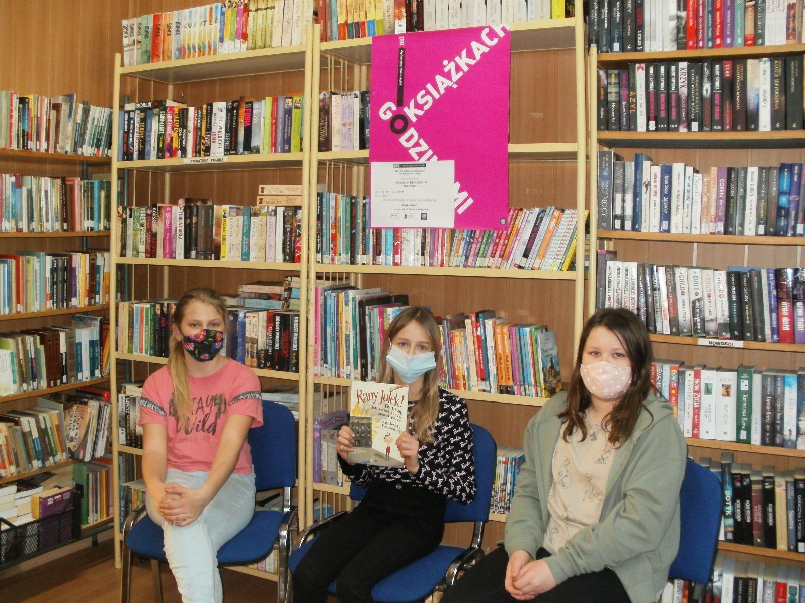 Zdjęcie. Na tle regałów bibliotecznych z książkami na niebieskich krzesłach siedzą trzy uczennice. Środkowa trzyma w rękach przeczytaną książkę. Nad nimi wisi różowy plakat O książkach Godzinami. Wszystkie mają na twarzach maseczki.